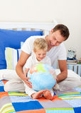 Laughing father and his son looking at a globe. Laughing father and his son looking at a terrestrial globe sitting on bed stock image