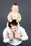 Laughing father holding his smiling little son on Stock Image