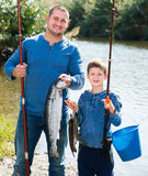 Laughing father and son fishing with rods. In summer day Royalty Free Stock Image