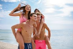 Laughing fellows in swimming trunks holding beautiful girls on a seashore on a blurred natural background. Attractive smiling guys holding appealing girls in Royalty Free Stock Images