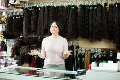 Laughing female assistant selling natural wigs Royalty Free Stock Image