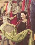 Laughing female customer examining sleeping bags Royalty Free Stock Image