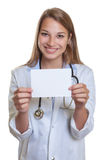 Laughing female doctor with blond hair showing card Royalty Free Stock Photo