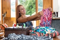 Female dressmaker at work with colorful clothes. Laughing female dressmaker at work with colorful clothes royalty free stock image
