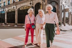 Laughing female friends in age are going across road royalty free stock photo