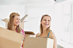 Laughing female friends holding boxes after moving