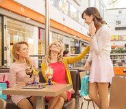 Laughing female friends in the shopping mall cafe Stock Photo