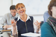 Laughing female mature woman sitting in classroom Royalty Free Stock Image