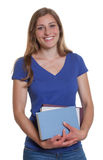 Laughing female student with blonde hair and books Stock Photos