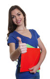 Laughing female student with long dark hair and paperwork showing thumb Royalty Free Stock Images