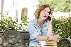 Laughing Female Student Outside Using Cell Phone Sitting on Bench. Smiling Young Pretty Female Student Outside on Cell Phone with Backpack and Books Sitting on Royalty Free Stock Photography