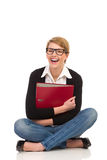 Laughing female student sitting with crossed legs. Royalty Free Stock Photo
