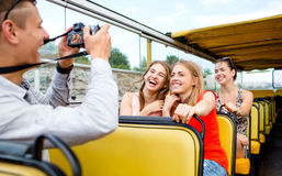 Laughing friends with camera traveling by tour bus. Friendship, travel, vacation, summer and people concept - laughing friends with camera traveling by tour bus Stock Images