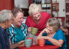 Laughing Friends in Coffeehouse stock images