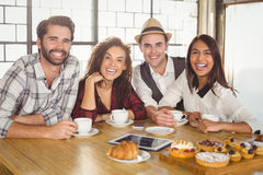 Laughing friends enjoying coffee and treats Stock Image