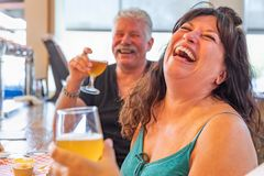 Laughing Friends Enjoying Glasses of Micro Brew Beer At Bar. Group of Friends Enjoying Glasses of Micro Brew Beer At a Bar stock photography