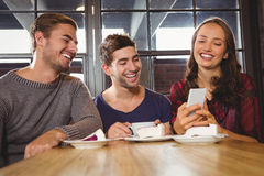 Laughing friends looking at smartphone Royalty Free Stock Photos