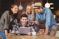 Laughing friends looking at tablet computer. At coffee shop Stock Image