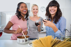 Laughing friends making spaghetti dinner together and drinking r. Ed wine at home in kitchen looking at camera Stock Image