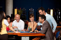 Laughing friends playing cards in a casino Royalty Free Stock Photo