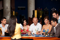 Laughing friends playing cards in a casino Royalty Free Stock Photography