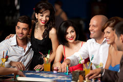 Laughing friends playing cards in casino stock photo