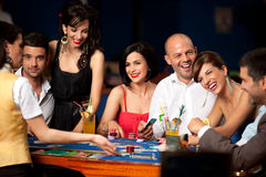 Laughing friends playing cards in a casino Royalty Free Stock Image