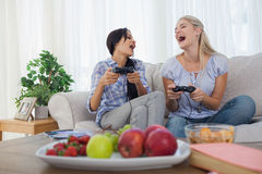 Laughing friends playing video games and having fun Royalty Free Stock Photo