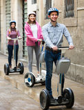 Laughing friends posing on segways on city street Royalty Free Stock Photography