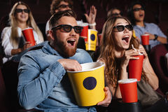 Laughing friends sitting in cinema watch film. Image of laughing friends sitting in cinema watch film eating popcorn and drinking aerated sweet water stock photos