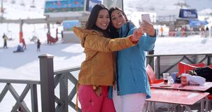 Laughing friends taking a selfie at a ski resort stock video footage