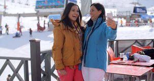 Laughing friends taking selfie at a ski resort Stock Photography