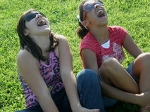 Laughing Fun. A picture of two girls who are best friends laughing in the grass Royalty Free Stock Images