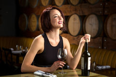 Laughing fun dating woman date night glass of wine at winery with barrels in background Royalty Free Stock Photography