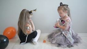 Laughing funny children sister girls in a witch costumes celebrating halloween. They have a lot of fun. stock video