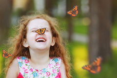 Laughing funny girl with a butterfly on his nose. Funny laughing curly girl with a butterfly on his nose. Healthy smile with white teeth. Free breathing concept Stock Photos