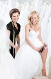 Laughing future bride in wedding gown. Puts the garter royalty free stock image