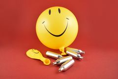 Laughing gas bombs stock images. Laughing gas balloons. Happy emoji balloon. Smiley inflatable balloon on a red background. Laughing party balloon. Nitrous oxide royalty free stock photos