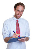 Laughing german businessman with clipboard Royalty Free Stock Image