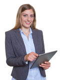 Laughing german businesswoman working with tablet computer Royalty Free Stock Photography