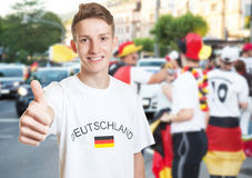 Laughing german fan showing thumb with other fans Stock Photos