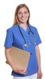 Laughing german nurse with file Royalty Free Stock Images