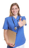 Laughing german nurse with file showing thumb up Royalty Free Stock Image