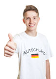 Laughing german soccer fan with blond hair showing thumb up Royalty Free Stock Images