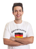 Laughing german sports fan with crossed arms and black hair Royalty Free Stock Images