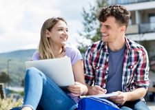 Laughing german student couple with computer stock photography