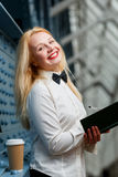 Laughing ginger woman in white shirt holding note-book. Stands next blue wall Royalty Free Stock Photography