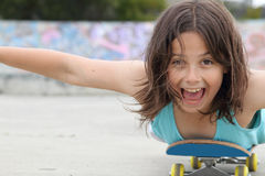 Laughing girl. Happy girl lying down on her skateboard as she rolls along stock photography