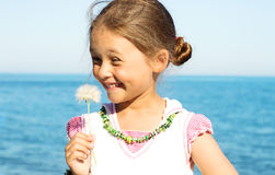 Laughing girl. Holding a ripe dandelion flower Royalty Free Stock Images
