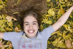 Laughing Girl. Beautiful young girl with big smiling on yellow autumn leaves royalty free stock photo